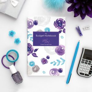 purple floral financial notebook on a desktop with a blue pen and calculator
