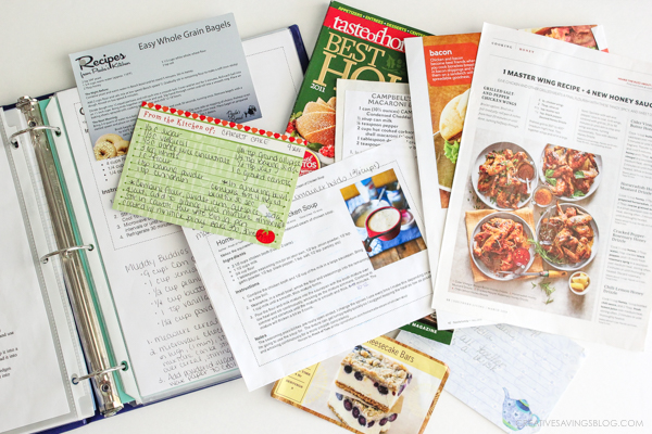 Photo of a recipe binder with a pile of disorganized recipes on top. It's time to clean this clutter up!