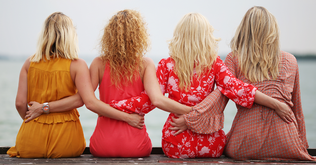 four girls with their arms around each other